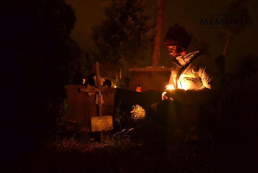 Prie kapavietės tamsoje sėdinti moteris laikanti rankoje žvakę