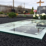 Kapo dizainas su mirusiojo nuotraukomis kapo viduje ir juodu paminklu Marijampolėje