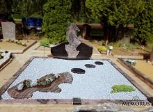 kapas užpiltas pilka skaldele ir dekoruotas granito gėlynu su akmens pėdutėmis ir augalais