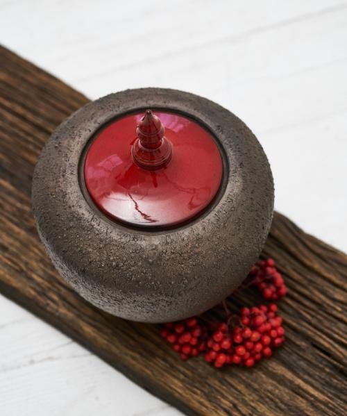 tamsiai ruda kremavimimo urna su blizganciu raudonu dangteliu